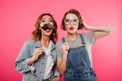Amis de dames drôles tenant la faux moustache et verres Photo libre de droits