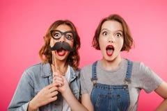 Amis de dames drôles tenant la faux moustache et verres Photos libres de droits