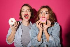 Amis de dames mangeant des butées toriques Image stock