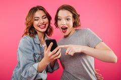 Amis de dames de sourire à l'aide du téléphone portable Photos stock
