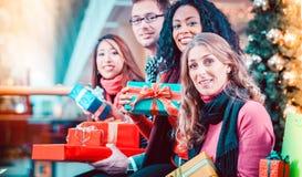 Amis de diversité avec des cadeaux de Noël et sacs faisant des emplettes en m Photos stock