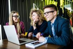 Amis de diversité employant le concept d'ordinateur portable à la table en café moderne Photos libres de droits