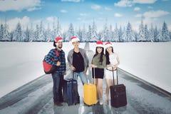 Amis de diversité portant des valises à l'hiver Photographie stock