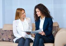 Amis de femme à la maison lisant Photographie stock libre de droits