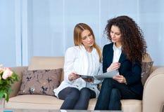 Amis de femme à la maison lisant Photos stock