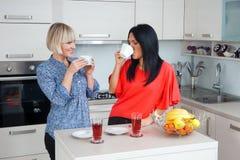 Amis de femme causant et buvant du café Photo stock