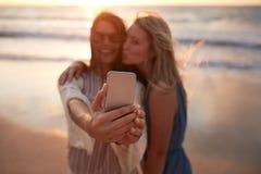 Amis de femme prenant le selfie à la plage Image libre de droits