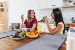 Amis de femmes ayant des fruits au petit déjeuner dans la cuisine Photographie stock libre de droits