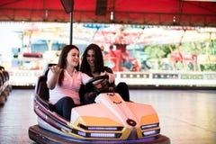 Amis de femmes ayant l'amusement au parc d'attractions, conduisant la voiture de butoir Photos stock