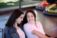 Amis de femmes ayant l'amusement au parc d'attractions, conduisant la voiture de butoir Photographie stock libre de droits