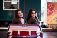 Amis de femmes ayant l'amusement au parc d'attractions, conduisant la voiture de butoir Images stock