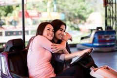 Amis de femmes ayant l'amusement au parc d'attractions, conduisant la voiture de butoir Photos libres de droits