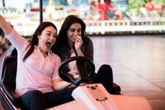Amis de femmes ayant l'amusement au parc d'attractions, voiture de butoir Image libre de droits