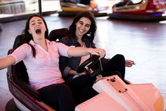 Amis de femmes ayant l'amusement au parc d'attractions, voiture de butoir Photo stock