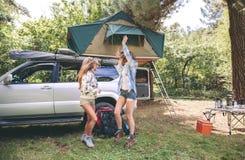 Amis de femmes ayant l'amusement dans le terrain de camping dans la forêt Images stock