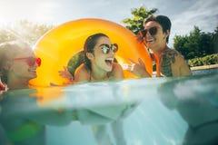 Amis de femmes ayant l'amusement ensemble dans la piscine Photo stock