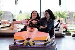 Amis de femmes conduisant la voiture de butoir en parc d'attractions, ayant l'amusement Photos libres de droits