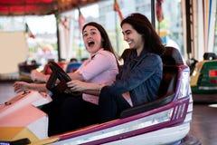 Amis de femmes conduisant la voiture de butoir en parc d'attractions, ayant l'amusement Photographie stock