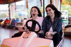 Amis de femmes conduisant la voiture de butoir en parc d'attractions, ayant l'amusement Image stock