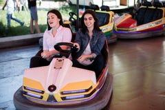 Amis de femmes conduisant la voiture de butoir en parc d'attractions, ayant l'amusement Images libres de droits