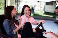 Amis de femmes conduisant la voiture de butoir en parc d'attractions, ayant l'amusement Photo stock