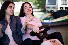 Amis de femmes conduisant la voiture de butoir en parc d'attractions, ayant l'amusement Image libre de droits