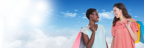 Amis de femmes faisant des emplettes avec des sacs et la transition de ciel Photographie stock