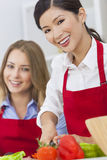 Amis de femmes préparant la nourriture de salade de légumes dans la cuisine Photographie stock libre de droits