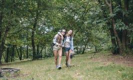 Amis de femmes riant tout en marchant dans la forêt Photo stock