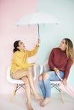 Amis de femmes s'asseyant dans le salon avec le parapluie Photographie stock libre de droits