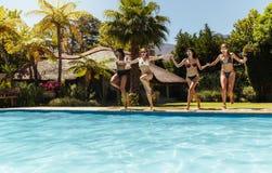 Amis de femmes sautant dans la piscine Images libres de droits