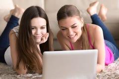 Amis de femmes se trouvant sur le plancher devant l'ordinateur portable Photos stock