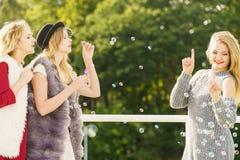 Amis de femmes soufflant des bulles de savon Photo libre de droits