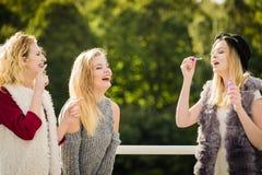 Amis de femmes soufflant des bulles de savon Images stock