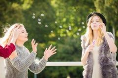 Amis de femmes soufflant des bulles de savon Photographie stock libre de droits