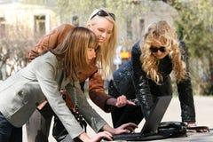 Amis de femmes travaillant avec l'ordinateur portatif extérieur Photos stock