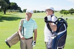 Amis de golfeur causant et tenant leurs sacs de golf Photographie stock libre de droits