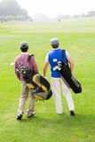 Amis de golfeur marchant et causant Photographie stock libre de droits