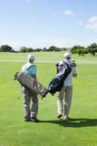 Amis de golfeur marchant et tenant leurs sacs de golf Photographie stock libre de droits