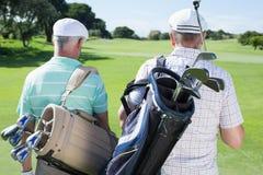 Amis de golfeur marchant tenant leurs sacs de golf Photographie stock