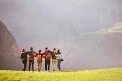 Amis de groupe étreignant contre la vallée de montagnes Photos stock