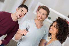Amis de groupe ayant le karaoke d'amusement chantant à la maison Image libre de droits