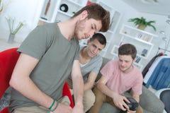 Amis de groupe employant la technologie numérique à la maison Photographie stock