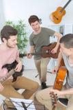Amis de groupe jouant la guitare à la maison Images stock