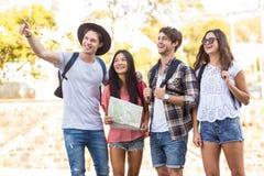 Amis de hanche allant sur une promenade et vérifiant la carte Photographie stock libre de droits