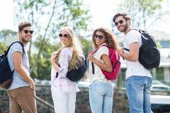 Amis de hanche avec des sacs à dos regardant de retour l'appareil-photo Images libres de droits