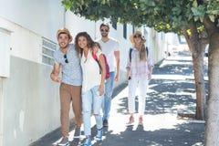 Amis de hanche marchant sur la rue Photographie stock