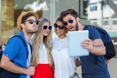 Amis de hanche prenant le selfie avec le comprimé Images libres de droits
