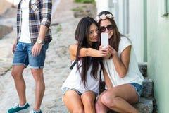Amis de hanche prenant le selfie se reposant sur des étapes Image libre de droits