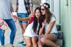 Amis de hanche prenant le selfie se reposant sur des étapes Photos stock